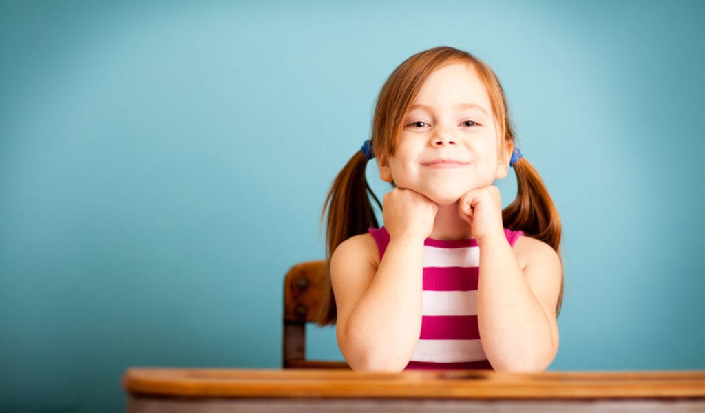 young female child sitting at desk at school