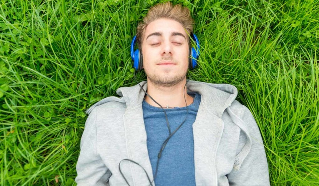 teen boy laying on grass listening to music