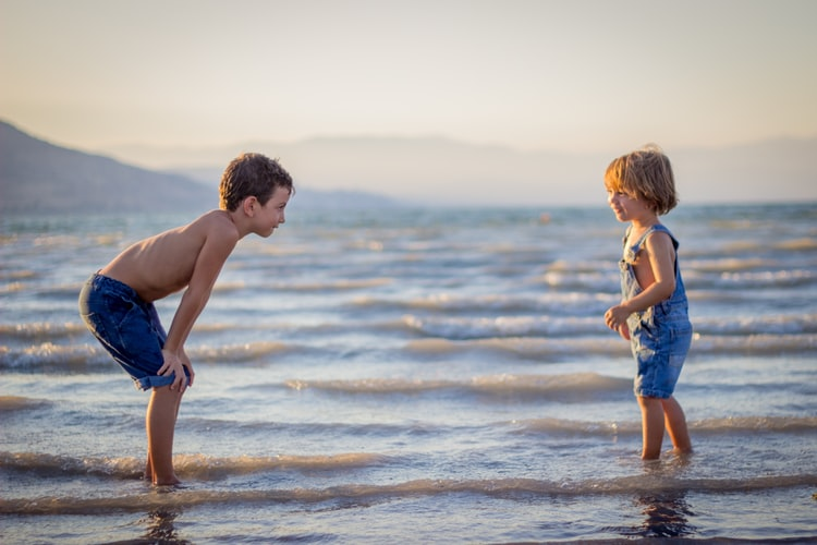 two children stand in water